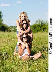 Three happy teen girls embracing against blue sky