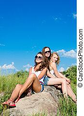 Three happy teen girls embracing against blue sky