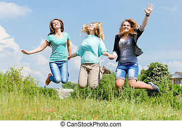 Three happy teen girls friends jumping high in blue sky