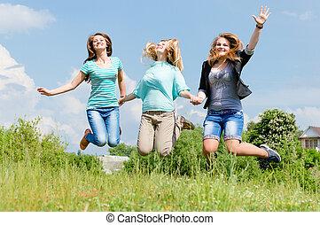 Three happy teen girls friends jumping high in blue sky