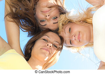 Three happy teen girls looking down against blue sky