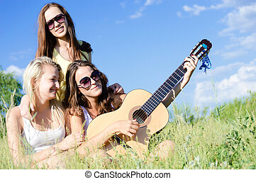 Three happy teen girls singing and playing guitar against blue sky