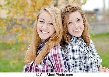 Three happy teen school girls friends outdoors