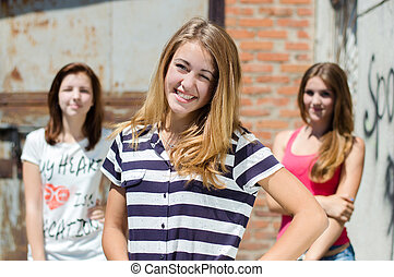 Three happy teenage friends smiling at urban background on summer day