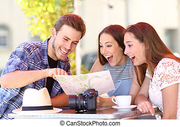 Three happy tourists checking guide in a coffee shop