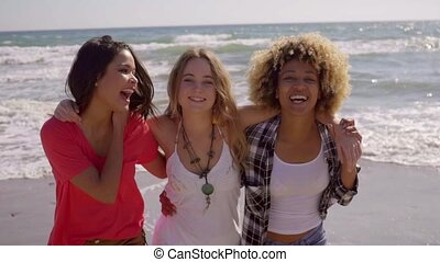 Three happy vivacious multiracial girl friends standing arm...