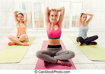 Three happy women doing stretching