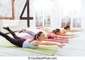 Three happy women exercising hard in fitness studio