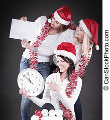 three happy women in costume of Santa Claus with clock, and Chri