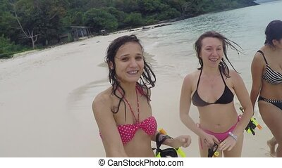 Three happy women wearing bikinis partying at the beach going with snorkeling masks in their hands.