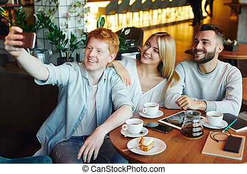 Three happy young affectionate friends making selfie in cozy cafe by cup of tea