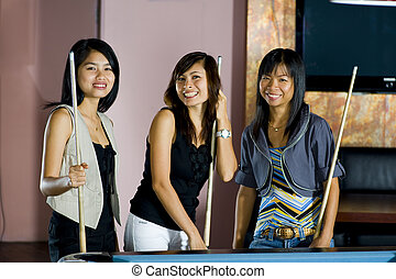 three happy young asian women standing next to a pool table