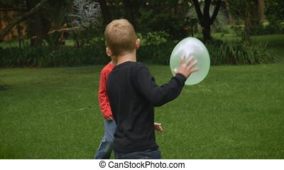 Three happy young children play a game in a park with...