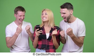 Three happy young friends using phone together and looking...