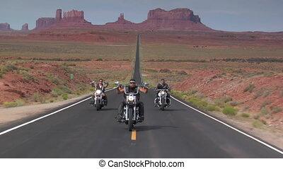 Three Harley motorcycles drive desert highway