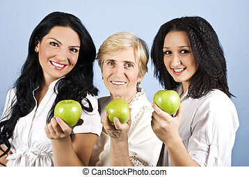 Three healthy beauty women giving you apples