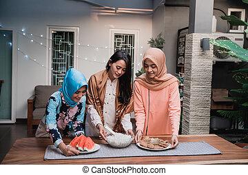 three hijab woman preparing food to serve when breaking fast...