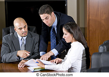 Three Hispanic office workers reviewing report