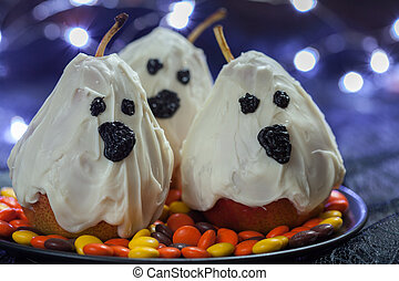 Halloween candy pears or white chocolate ghosts on a stick -...