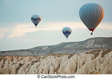 Three hot air balloons flying over the rocks of Cappadocia