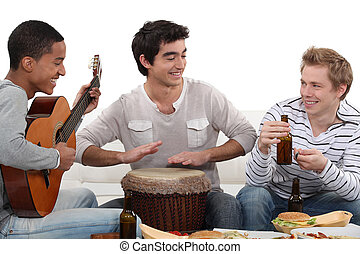 Three house-mates eating burgers and playing music