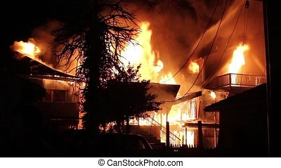 3 houses burning side by side in residential neighborhood at night