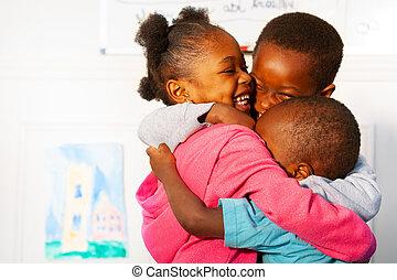 Three hugging close black kids in nursery class