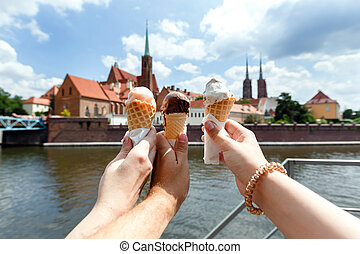 Three human hands hold ice cream on a background of a old churches of the historic center of Wroclaw.