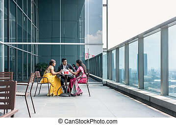 Three Indian business people talking during break at work
