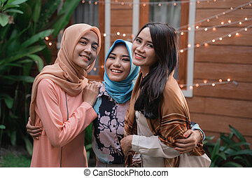 Three islam women standing on the backyard while look at...