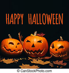 Three Jack-o ' - lantern pumpkins on a black background with maple leaves