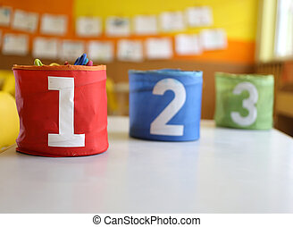 Three jars colored Red Green and blue with written one two and three on the table in the kindergarten classroom