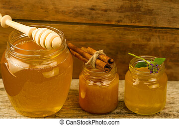 three jars of honey with drizzler, cinnamon, flowers on...