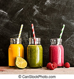 Three large mason jars of yellow green and pink tropical fruit beverages with straws on a long rustic table next to raspberries and a cut lime