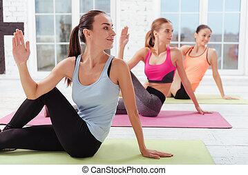 Three joyful women doing stretching exercise