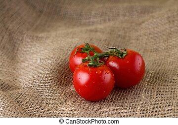 Three juicy tomatoes on jute cloth