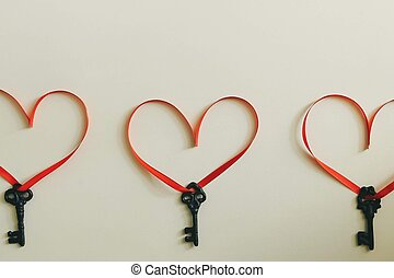 Three keys with a red ribbon in the shape of a heart on a light surface