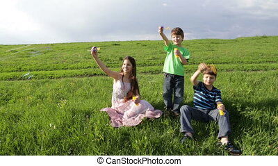 Three kids blowing up the soap bubbles on the hill