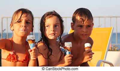 Three kids eat ice cream in waffle cone, little girl shows...