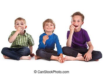 three kids eating sweets