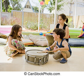three kids in the backyard having fun with drums.