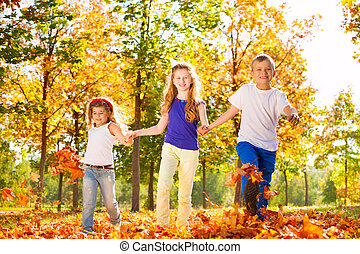 Three kids hold hands playing in the forest