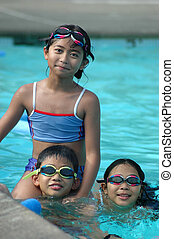 Three smiling children in the pool
