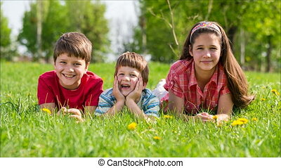 Three kids lying together on green meadow