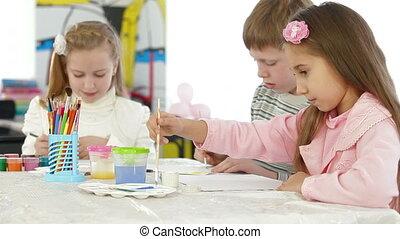 three kids painting in watercolor