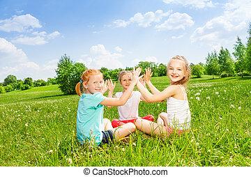Three kids playing on a grass