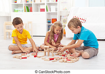 Three kids playing with wooden blocks