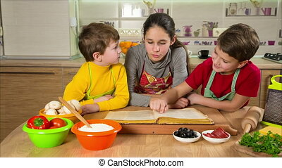 Three kids reading the cook book, making the dinner