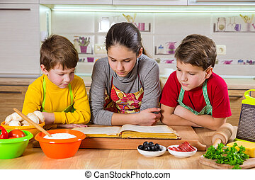 Three kids reading the cook book