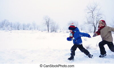 Three kids running together on winter landscape